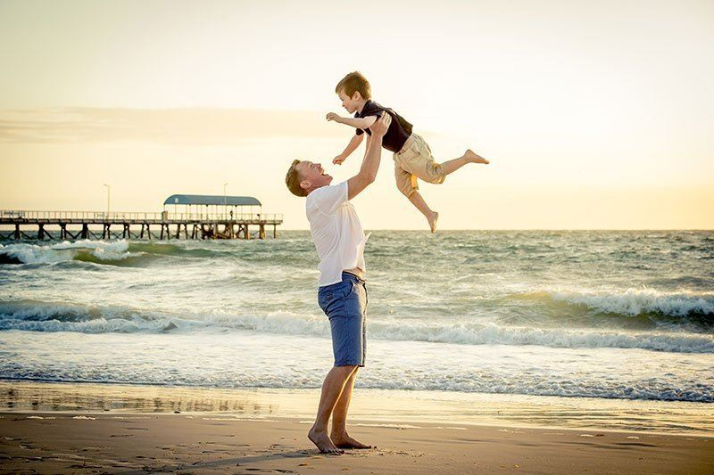 Father lifting son up into the air by the beach